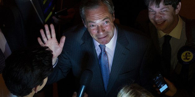 UK Independence Party (UKIP) leader Nigel Farage (C) waves as he speaks to the media at the Southampton Guildhall announcement of the South East England region results from the European Parliament elections in Southampton, southern England, on May 25, 2014. Results starting rolling in the European Parliament elections with all eyes on potential gains by Europe's increasingly popular anti-EU parties. Farage, leader of the eurosceptic UKIP, on May 25 said his party was on course to cause a politic