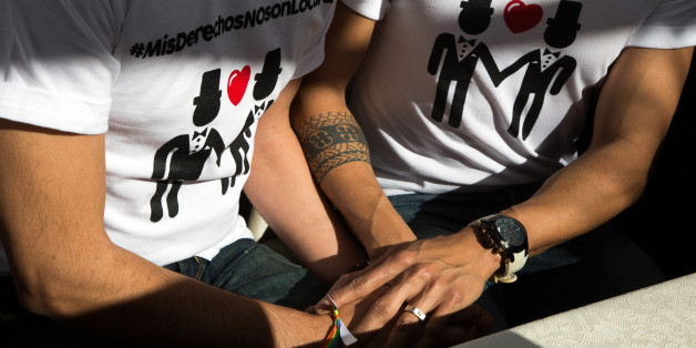 Victor Fernando Urias, left, and Victor Manuel Aguirre hold hands while getting married during a protest outside of the municipal palace in the northern border city of Mexicali, Mexico, Saturday Jan., 17, 2015. The protest was held against Mexicali's mayor and other officials after blocking for a fourth time the gay couple from marrying in defiance of an order from Mexico's Supreme Court, the men's lawyer said. Hours later, the Mayor allowed the couple to marry. (AP Photo/Alex Cossio)
