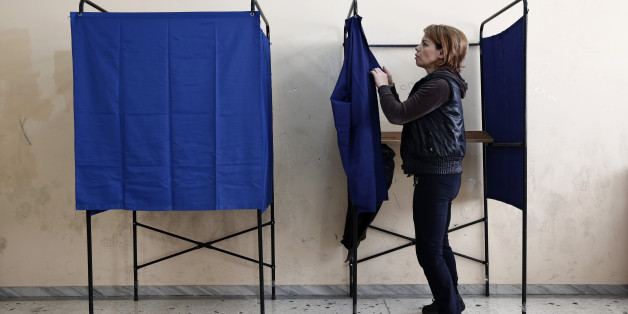 A municipal worker assembles voting booths at a voting center, in Athens, Friday, Jan. 23, 2015. Prime Minister Antonis Samaras' New Democracy party has failed so far to overcome a gap in opinion polls with the anti-bailout Syriza party ahead of the Jan. 25 general election. (AP Photo/Petros Giannakouris)