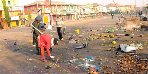 Nigerian security inspect the scene of a bomb blast at the Jos Terminus Market, on December 12, 2014. A double bomb attack that killed 31 people in a crowded market in the central Nigerian city of Jos was likely to have been carried out by Boko Haram, the state government said. 'It's an extension of the terrorist acts that have been penetrating all states and cities,' Pam Ayuba, spokesman for the Plateau state governor Jonah Jang, told AFP by telephone. AFP PHOTO/STRINGER        (Photo credit sh