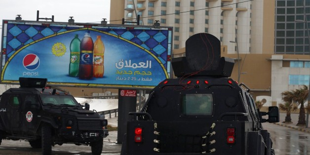 Libyan security forces surround Tripoli's central Corinthia Hotel (R) on January 27, 2015 in the Libyan capital. The hotel was reportedly attacked by Islamist gunmen today and gunfire was heard, an AFP photographer reported. According to security sources at the scene, four armed men had detonated a car bomb in front of the Corinthia Hotel, which is popular with foreigners, killing a guard, before rushing into the hotel. AFP PHOTO/MAHMUD TURKIA        (Photo credit should read MAHMUD TURKIA/AFP/Getty Images)