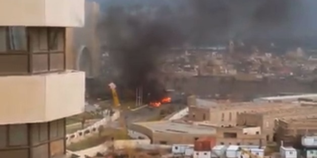 An image grab taken from an AFPTV video shows fire and smoke rising in front of the Corinthia hotel in Tripoli on January 27, 2015 after gunmen stormed the luxury hotel. Gunmen stormed the hotel in Libyan capital popular with diplomats and officials in an attack claimed by the Islamic State group, killing at least nine people including five foreigners before blowing themselves up. AFP PHOTO / AFPTV        (Photo credit should read STR/AFP/Getty Images)