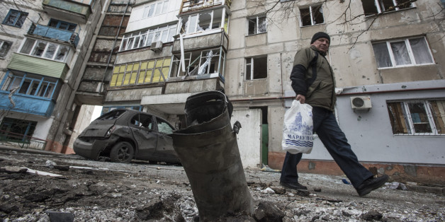 A man walks by a burned car and a piece of exploded Grad missile, outside an apartment building in Vostochniy district of Mariupol, Eastern Ukraine, Sunday, Jan. 25, 2015. Indiscriminate rocket fire slammed into a market, schools, homes and shops Saturday in Ukraine's southeastern city of Mariupol, killing at least 30 people, authorities said. The Ukrainian president called the blitz a terrorist attack and NATO and the U.S. demanded that Russia stop supporting the rebels. (AP Photo/Evgeniy Maloletka)