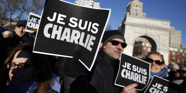 """Attendees hold """"Je Suis Charlie"""" (I am Charlie) signs as several hundred people gather in solidarity with victims of two terrorist attacks in Paris, one at the office of weekly newspaper Charlie Hebdo and another at a kosher market, in New York's Washington Square Park, Saturday, Jan. 10, 2015. (AP Photo/Jason DeCrow)"""