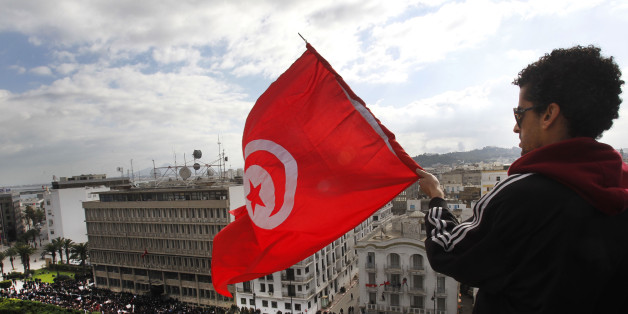 A protester waves the Tunisian flag as he watches a demonstration against President Zine El Abidine Ben Ali, in Tunis, Friday, Jan. 14, 2011. Thousands of angry demonstrators marched through Tunisia's capital Friday, demanding the resignation of the country's autocratic leader a day after he appeared on TV to try to stop deadly riots that have swept the North African nation. (AP Photo/Christophe Ena)