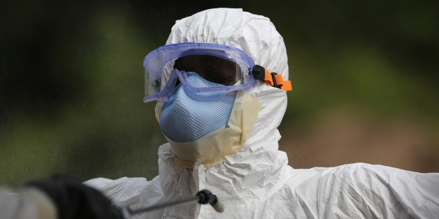 DISCO HILL, LIBERIA - JANUARY 27:  A burial team member wearing personal protective equipment (PPE), stands for decontamination spray at the U.S.-built cemetery for 'safe burials' on January 27, 2015 in Disco Hill, Liberia. The cemetery, operated by USAID-funded Global Communities, has buried almost 300 people in its first month of operation, with increasingly fewer of the bodies coming from Ebola Treatment Units (ETUs), as infection rates decline. The cemetery, where burial team members wear protective clothing, has been seen in Monrovia as a major achievement, as families of deceased loved ones are permitted to view the burials, important in Liberian culture. In an effort to control the Ebola epidemic in 2014, the Liberian government had ordered the cremation of all deceased in the capital, often further traumatizing surviving family members and unintentionally encouraging many families to hide their dead for secret burials.  (Photo by John Moore/Getty Images)