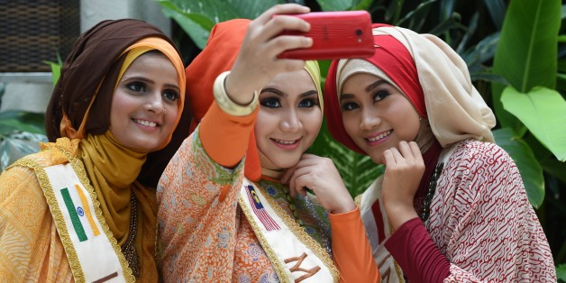 From L-R: Nazreen of India, Nur Khairunnisa of Malaysia, and Lulu Susanti of Indonesia, three of the finalists in the World Muslimah Awards, pose for a selfie as they wear Indonesian handmade 'batik' creations from the Danar Hadi collection in Yogyakarta on November 20, 2014. Indonesia is hosting the 4th World Muslimah Awards beauty pageant, exclusive to Muslim women, in Yogyakarta from November 13-21. AFP PHOTO / ADEK BERRY        (Photo credit should read ADEK BERRY/AFP/Getty Images)