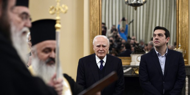 Newly elected Greek Prime Minister Alexis Tsipras (R) and President Carolos Papaoulias look on as the new government's take the civil oath, during a ceremony at the Presidental Palace in Athens, on January 27, 2015.  Tsipras, the leader of the Syriza leftist party, has raised fears of a possible Greek exit from the single currency area by vowing to reduce the huge debt payments Greece has to make following its international bailouts. AFP PHOTO / LOUISA GOULIAMAKI        (Photo credit should read