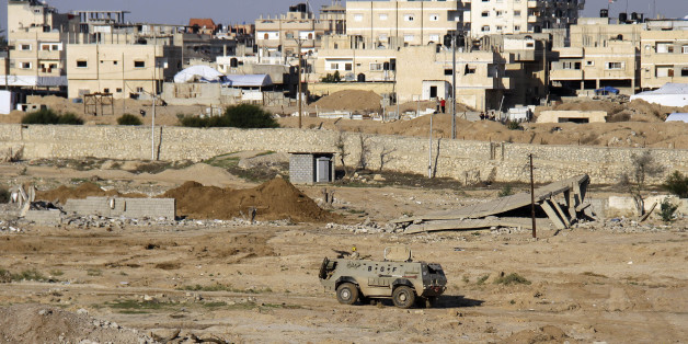 In this Thursday, Nov. 6, 2014 photo, an Egyptian army armored vehicle stands on the on the Egyptian side of border town of Rafah, northeast of Cairo, Egypt. In the deadliest-ever militant attack on the military, at least 30 soldiers were killed late last month in Sinai, prompting President Abdel-Fattah el-Sissi to declare a state of emergency in northern Sinai and order the eviction of some 10,000 people from the town of Rafah on the border with the Gaza Strip.(AP Photo/Ahmed Abd El Latif, El Shorouk Newspaper) EGYPT OUT