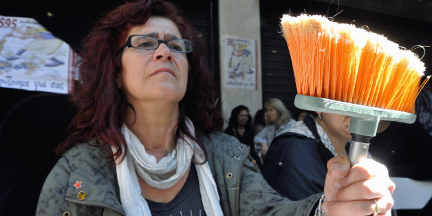 ATHENS, GREECE - 2014/05/07: A cleaning lady, a former employee in the ministry of Finance in Greece holds a mop symbol of her work and a sign of protest. Hundreds of people took part in a protest, demanding that the Greek government revokes its decision to lay off public sector workers under the financially troubled country's bailout commitments. (Photo by George Panagakis/Pacific Press/LightRocket via Getty Images)