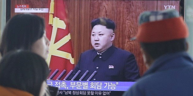 """People watch a TV news program showing North Korean leader Kim Jong-Un delivering a speech, at the Seoul Railway Station in Seoul, South Korea, Thursday, Jan. 1, 2015. Kim, in a nationally televised New Year's Day speech, says he is open to a summit with his South Korean counterpart. The letters read: """"Meeting."""" (AP Photo/Ahn Young-joon)"""