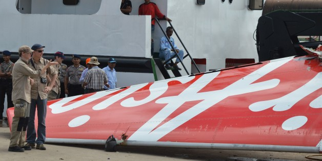 Foreign investigators (L) examine the tail of the AirAsia flight QZ8501 in Kumai on January 12, 2015, after debris from the crash was retrieved from the Java sea. Indonesian divers retrieved the flight data recorder of the AirAsia plane that went down in the Java Sea a fortnight ago with 162 people on board, a crucial breakthrough that should help explain what caused the crash. AFP PHOTO        (Photo credit should read STR/AFP/Getty Images)