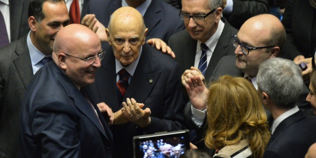 Italy's former President, Giorgio Napolitano (C) surrounded by Italian senators, deputies and representatives of the regions -- members of the electoral college -- applauds newly elected Italian President, Sicilian judge Sergio Mattarella, on January 31, 2015, at the Parliament in Rome. Renzi's backing for Mattarella has been interpreted as the end of a temporary alliance the premier forged with disgraced former prime minister Silvio Berlusconi to help drive labour market and electoral reforms through parliament. Mattarella is seen as an 'anti-Berlusconi' figure, having severed his ties with the centre right in Italian politics partly because of his distaste for the media tycoon, who still heads the opposition Forza Italia party despite a tax fraud conviction.  AFP PHOTO / ANDREAS SOLARO        (Photo credit should read ANDREAS SOLARO/AFP/Getty Images)