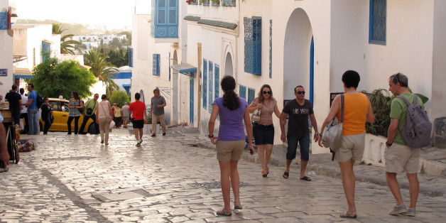 Tunisian and foreign tourists wander through the picturesque town of Sidi Bou Said just outside the Tunisian capital of Tunis on July 1, 2012. After a disastrous year in which revolution, social upheaval and strikes scared away tourists and crippled industrial production, the economy is slowly climbing out of a deep recession that saw it shrink by 2 percent in 2011. (AP Photo/Paul Schemm)