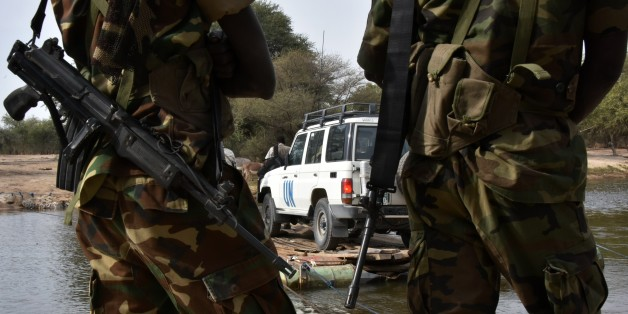 A picture taken on January 27, 2015 shows Chadian soldiers watching as a UN vehicle from a United Nations' refugee agency (UNHCR) convoy crosses a branch of lake Chad, heading to the UNHCR camp in N'Gouboua, in Chad's Lake Chad region. Since the beginning of January more than 14,000 people have fled over the Nigerian border into Chad to escape the bloody attacks by Islamist group Boko Haram around Baga, according to Mamadou Dian Balde, of the UN's refugee agency.  AFP PHOTO/ SIA KAMBOU        (Photo credit should read SIA KAMBOU/AFP/Getty Images)