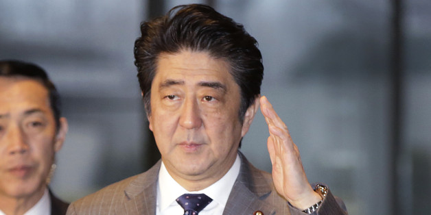 Japan's Prime Minister Shinzo Abe, right, arrives at the prime minister's official residence in Tokyo, Friday, Jan. 30, 2015. (AP Photo/Eugene Hoshiko)