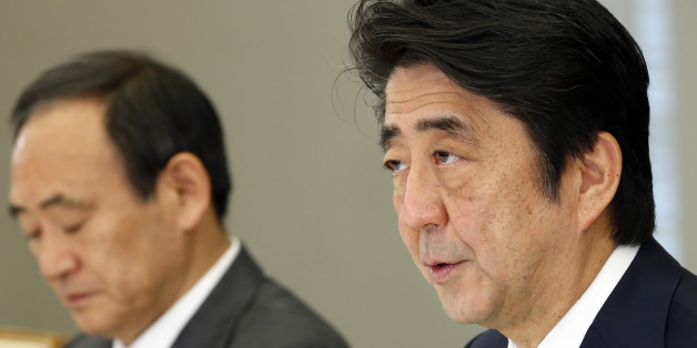 Japan's Prime Minister Shinzo Abe, right, accompanied by government spokesman Yoshihide Suga, speaks during a hurriedly held ministerial meeting on Japanese hostage Kenji Goto taken by the Islamic State group, at the prime minister's official residence in Tokyo Thursday, Jan. 29, 2015. The extremist group released a message late Wednesday purportedly extending the deadline for Jordan's release of an Iraqi would-be hotel bomber linked to al-Qaida. The message, read by a voice claiming to be Goto, was released online after Jordan offered a precedent-setting prisoner swap to the Islamic State group, desperately seeking to save a Jordanian air force pilot the militants purportedly threatened to kill, along with Goto. Suga said on Thursday the government was analyzing the latest message and Japan was doing its utmost for the release of Goto, working with nations in the region, including Turkey, Jordan and Israel. (AP Photo/Shizuo Kambayashi, Pool)