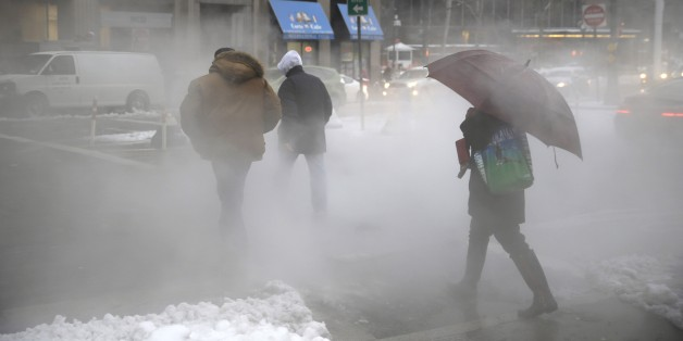 "Pedestrians make their way around lower Manhattan on slushy morning in New York, Monday, Feb. 2, 2015.  New York City Mayor Bill de Blasio is warning commuters to be ""very cautious"" as another winter storm system brings a mix of snow, sleet and freezing rain to the metro area. (AP Photo/Seth Wenig)"