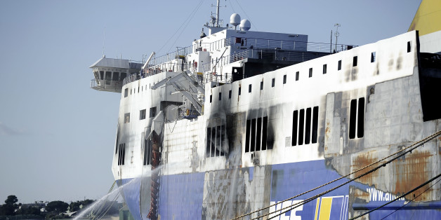 BRINDISI, ITALY - JANUARY 07:  The hull of the burned-out ferry 'Norman Atlantic' is cooled by firemen as it stands moored in port on January 07, 2015 in Brindisi, Italy. Yesterday firemen have measured the temperature on the ferry in order to give permission to the police investigators to go aboard and to find out the cause of the fire, but it is still unclear when investigators will access the ferry. So far police has been unable to gain access deep inside the vessel in the their search for more bodies as temperatures inside the hull from the fire that struck the ship remain too high and heavy winds hit the coast of south-east Italy. The Italian-owned ferry caught fire on December 28, 2014, on its journey from Patras in Greece to Ancona in Italy. At least 11 people are confirmed dead as a result of the blaze and 477 survived after being rescued by the Italian Coast Guard and Navy, though 19 passengers remain unaccounted for and are presumed to likely be dead and still inside the ship.  (Photo by Alexander Koerner/Getty Images)