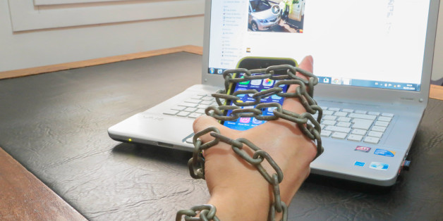 Guy chained to smartphone and internet laptop. Conceptual picture for internet addiction.