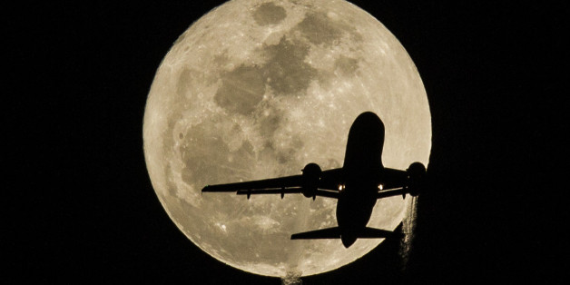 Feb. 3, 2015 - Los Angeles, California, U.S - An airplane approaching Los Angeles International Airport flies in front of the moon