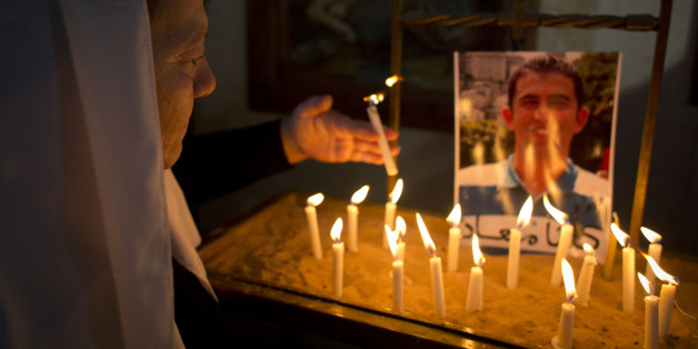 A Jordanian Christian lights a candle next to a picture of Jordanian pilot Lt. Muath al-Kaseasbeh, who is being held by Islamic State group militants, following Sunday prayers in Adir Roman Catholic Church, on the outskirts of Karak, Jordan, Sunday, Feb. 1, 2015. Jordan renewed an offer Sunday to swap Sajida al-Rishawi, an al-Qaida prisoner, for a fighter pilot held captive by the Islamic State group, a day after a video purportedly showed the militants beheading Japanese journalist Kenji Goto.
