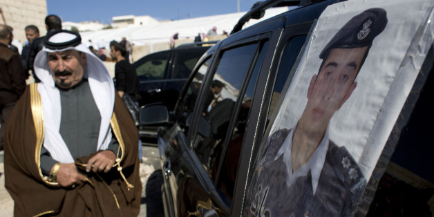 "A Jordanian man walks past a poster that is pasted on a vehicle with a picture of slain Jordanian pilot, Lt. Muath al-Kaseasbeh with Arabic that reads, ""we are all Muath,"" at his home village of Ai, near Karak, Jordan, Wednesday, Feb. 4, 2015. Outrage and condemnation poured across the Middle East on Wednesday as horrified people learned of the video purportedly showing the Islamic State group burn a Jordanian pilot to death. (AP Photo/Nasser Nasser)"