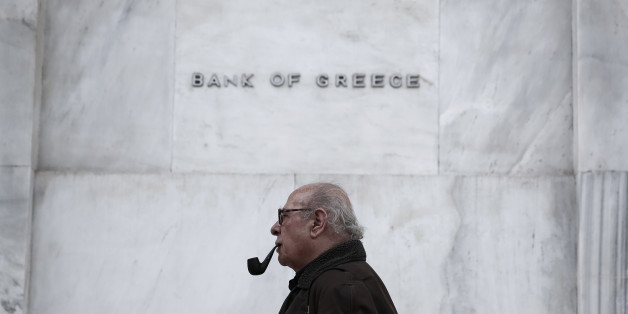 A man walks past  the Bank of Greece headquarters, in central Athens, on Wednesday, Feb. 4, 2015. With all Europe waiting to see how Greece proposes to renegotiate its massive bailout loans, Greece's Prime Minister Alexis Tsipras and his Finance Minister Yanis Varoufakis are on a whirlwind tour of the region to discuss possible solutions. Tsipras wants easier terms of repayment on the 240 billion euros (currently $271 billion) in bailout loans and to ease back on the austerity budget measures th