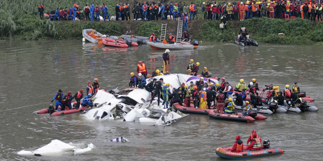 Emergency personnel try to extract passengers from a commercial plane after it crashed in Taipei, Taiwan, Wednesday, Feb. 4, 2015. The Taiwanese commercial flight with 58 people aboard clipped a bridge shortly after takeoff and crashed into a river in the island's capita on Wednesday morning.  (AP Photo/Wally Santana)