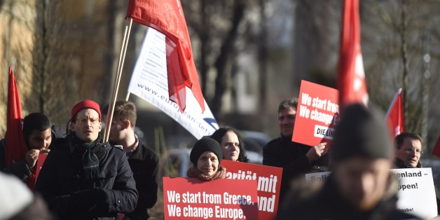 Protestors hold a sign reading 'We start from Greece, we change Europe' during a demonstration in front of the German Finance minstry ahead of a meeting of Greece's new Finance Minister with his German counterpart in Berlin, on February 5, 2015. Greece's new finance minister Yanis Varoufakis faces tough talks with his German counterpart Wolfgang Schaeuble after the European Central Bank piled fresh pressure on Athens by restricting Greek banks' access to much-needed cash. AFP PHOTO / ODD ANDERSEN        (Photo credit should read ODD ANDERSEN/AFP/Getty Images)