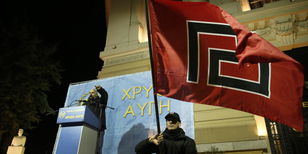 Ilias Panagiotaros,  left, a member of the Greek Parliament of the extreme far-right party Golden Dawn, gestures as he talks during a rally to commemorate a 1996 incident which cost the lives of three Greek navy officers and brought Greece and Turkey to the brink of war, in central Athens, Saturday, Jan. 31, 2015. The extreme right, anti-immigrant Golden Dawn party, which has Nazi roots, received the third-place in Sunday, Jan. 25's election. Its showing comes despite the fact that the party's leader and most of its lawmakers are behind bars, facing charges of participating in a 'criminal organization' accused of murders, brutal attacks on migrants and others, extortion and arson. (AP Photo/Lefteris Pitarakis)
