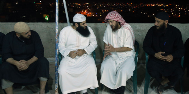 YAJUZ, JORDAN- JUNE 16: Essam Barqawi (2nd from R), known as Abu Mohammad Al Maqdessi, talks with Qatada, the eldest son of the radical cleric Abu Qatada, who was deported to Jordan from the UK in July 2013, as Al Maqdisi is receiving guests greeting him at his home June 16, 2014 in Yajuz, east of Amman, Jordan. Jordan released the leading jihadist ideologist Al Maqdisi, who was once mentor to Iraq's now slain Al Qaida leader, on Monday after he completed a jail sentence for recruiting fighters for the Taliban. (Photo by Jordan Pix/ Getty Images)