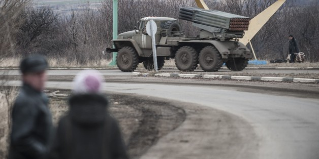 "A Ukrainian multiple rocket launcher system BM-21 ""Grad"" is driven on a road near Artemivsk, eastern Ukraine, Thursday, Feb. 5, 2015. Fighting between Russia-backed separatists and Ukrainian forces in eastern Ukraine surged in January, raising the death toll to over 5,300 people killed since April. In a new push for peace, the leaders of France and Germany headed Thursday to Kiev and Moscow with a proposal to end the fighting in eastern Ukraine. (AP Photo/Evgeniy Maloletka)"
