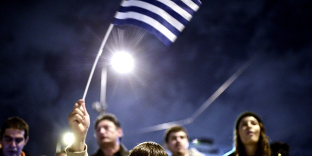 A young child waves the national flag as crowds gather in front of the Greek parliament in Athens on February 5, 2015  in support of the new anti-austerity government's efforts to renegotiate Greece's international loans.  About 5,000 people gathered in Syntagma Square, police said, in front of the Greek parliament, the site of violent protests at the height of the Greek crisis in 2012. Many praised the government for 'defending the interests' of the Greek people. AFP PHOTO/ Louisa Gouliamaki        (Photo credit should read LOUISA GOULIAMAKI/AFP/Getty Images)