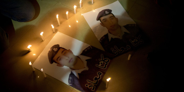 "Members of Al-Kaseasbeh, the tribe of Jordanian pilot, Lt. Muath al-Kaseasbeh, who is held by the Islamic State group militants, light candles by posters with his picture and Arabic that reads ""we are all Muath,"" at the captured pilot's tribal gathering divan, in his home town of Karak, Jordan, Saturday, Jan. 31, 2015. An online video released Saturday night purported to show an Islamic State group militant behead Japanese journalist Kenji Goto, ending days of negotiations by diplomats to save t"