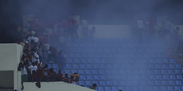 Police use tear gas on Equatorial Guinea supporters after the were throwing objects on the pitch During their African Cup of Nations Semifinals soccer match with Ghana  at Estadio De Malabo, Equatorial Guinea, Thursday Feb. 5, 2015. (AP Photo/Sunday Alamba)