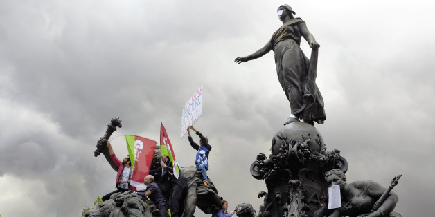 Union activists attend May Day celebrations, in Paris, Thursday May 1, 2014. Tens of thousands of workers marked May Day in European cities with a mix of anger and gloom over austerity measures imposed by leaders trying to contain the eurozone's intractable debt crisis. (AP Photo/Jerome Delay)