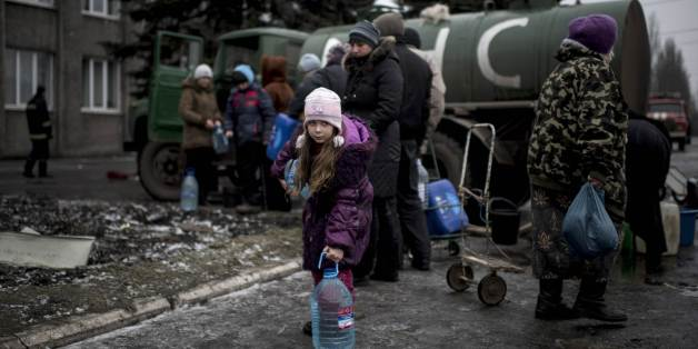 A girl holds a water bottle in the town of Debaltseve, eastern Ukraine, Friday, Feb. 6, 2015. Pro-Russia rebels and the Ukrainian authorities agreed Friday on a humanitarian corridor to evacuate civilians from the epicenter of fighting in eastern Ukraine as German and French leaders prepared to bring their peace plan to Moscow. (AP Photo/Evgeniy Maloletka)
