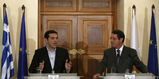 Greek Prime Minister Alexis Tsipras, left, speaks to the media as Cyprus' president Nicos Anastasiades listens during a press conference after their meeting at the Presidential Palace in the capital Nicosia, Monday, Feb. 2, 2015. Tsipras is visiting Cyprus, his first trip abroad as prime minister since his election last month. It's customary for all newly-elected Greek prime ministers to conduct their first trip abroad to Cyprus because of the two countries' deep historic ties. (AP Photo/Petros Karadjias)