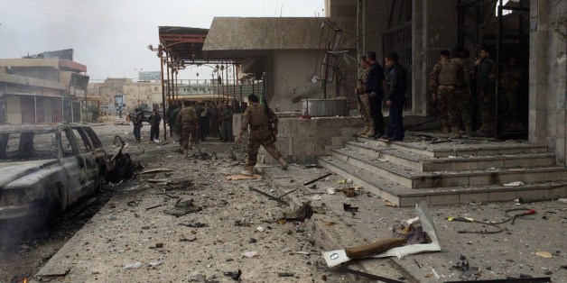 Kurdish peshmerga fighters secure a hotel near police headquarters in oil-rich Kirkuk, 290 kilometers (180 miles) north of Baghdad, Iraq, Friday, Jan. 30, 2015. Kurdish troops and the city's security force have been trying to rout militants from the Islamic State group after three gunmen took positions inside the hotel, located in the city center, triggering a firefight with Kurdish fighters and the police. (AP Photo)