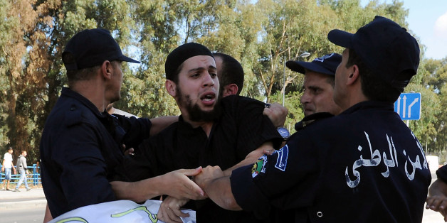 Algerian policemen arrest a demonstrator during a protest against an amateur film mocking Islam in Algiers on September 14, 2012. Anti-US protests by crowds whipped into fury by a film that mocks Islam erupted across the Muslim world, as violence exploded in Sudan, Lebanon, Tunisia and Yemen leaving five dead and dozens injured. AFP PHOTO/FAROUK BATICHE        (Photo credit should read FAROUK BATICHE/AFP/GettyImages)