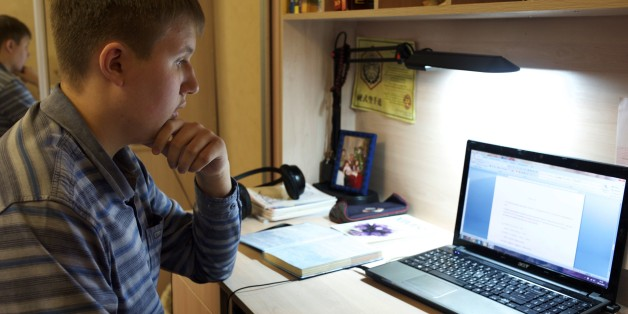 In this photo taken on Friday, Nov.  28, 2014, Denis Akimov, 15, sits in front of his laptop at home in Donetsk, eastern Ukraine. Like most children his age, Denis Akimov spends hours daily on his computer surfing the Internet. It isn't just for fun. As schools are forced to limit operations in the conflict-battered eastern Ukrainian city of Donetsk, educators are turning to the Web to keep their charges learning. (AP Photo/Balint Szlanko)