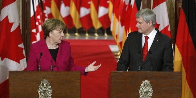 Chancellor Angela Merkel (L) and Canadian Prime Minister Stephen Harper (R) speak at a joint press conference on Parliament Hill in Ottawa, February 9, 2015. AFP PHOTO / Patrick DOYLE        (Photo credit should read PATRICK DOYLE/AFP/Getty Images)