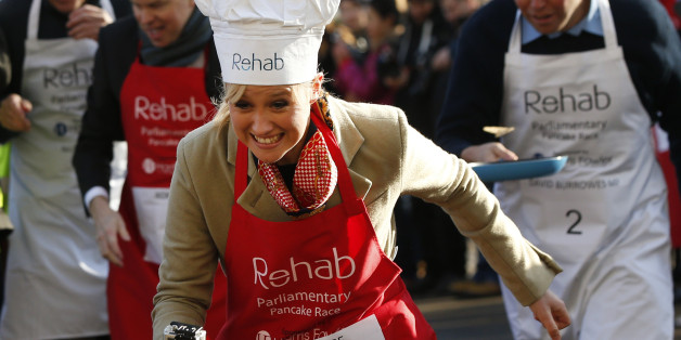 Media team competitor Sophie Ridge flips a pancake as she competes during the 2015 Parliamentary Pancake Race, Tuesday, Feb. 17, 2015. The race saw Lords, MPs and members of the parliamentary press corps racing to raise awareness of the need to support disable people, according to the organizers. (AP Photo/Lefteris Pitarakis)