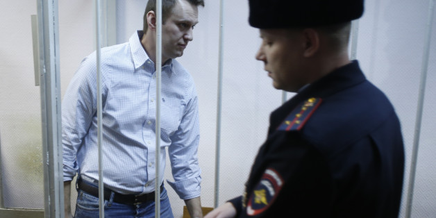 FILE - In this Tuesday, Dec. 30, 2014 file photo, Russian opposition activist Alexei Navalny, 38, enters a cage at a court in Moscow, Russia. Russia's leading opposition figure Alexei Navalny has been sentenced to 15 days in police custody for handing out leaflets in the subway. (AP Photo/Pavel Golovkin, File)