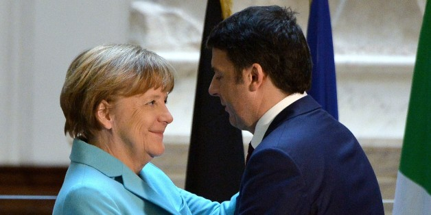 Italian Prime Minister Matteo Renzi (R) hugs German Chancellor Angela Merkel beneath the original 16th century statue of David by Italian artist Michelangelo Buonarroti during a joint press conference in the Galleria dell'Accademia in central Florence on January 23, 2015. The eurozone's deep divisions were set to be given an airing as Italian Prime Minister hosted German Chancellor Angela Merkel days before crucial elections in Greece. AFP PHOTO / ALBERTO PIZZOLI        (Photo credit should read