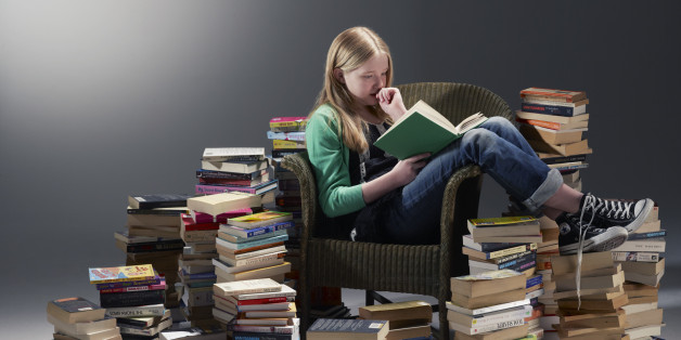 teenage girl sat in chair reading book surrounded by piles of books