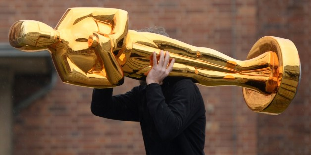 A worker carries an Oscar statue to a press event held by Filmstudios Babelsberg in Potsdam, eastern Germany following the sucess of the 'Grand Budapest Hotel' at the Oscars on February 23, 2015. The film, which was awarded 4 Oscars, Best original soundtrack, Best costume design, Best make-up / hairstyling and Best production design, was co-produced by Filmstudios Babelsberg. AFP PHOTO / DPA / RALF HIRSCHBERGER   +++ GERMANY OUT +++        (Photo credit should read RALF HIRSCHBERGER/AFP/Getty Im