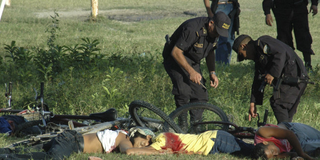 EDS. NOTE GRAPHIC CONTENT.- Police officers inspect the bodies of the victims of a massacre  at a soccer field in San Pedro Sula,  Honduras, Saturday Oct. 30, 2010.  A carful of attackers armed with assault rifles drove up to the football field  Saturday and opened fire, killing at least 14 people.(AP Photo)