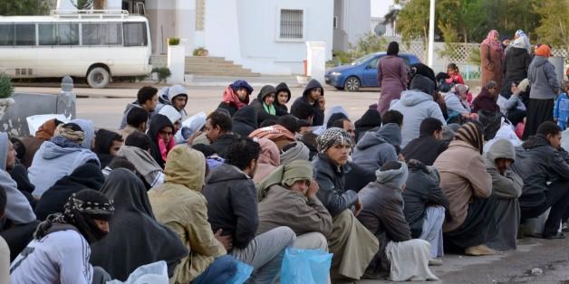 Des travailleurs égyptiens attendent après avoir franchi la frontière tunisienne au poste frontière de Ras Jdir, entre la Libye et la Tunisie, le vendredi 20 février.